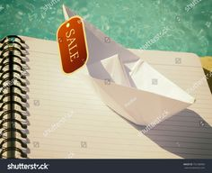 Boat For Sale.   A origami paper boat on a note pad at the edge of the water with a sale ticket hanging .