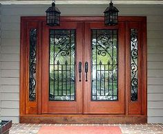 Wood front doors with cherry stain. Glass doors and sidelights with wrought iron. front door. double doors.  glass. wrought iron. iron.