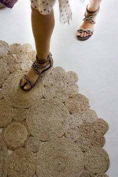 DIY Rustic Rug Of Jute Or Sisal Rope. Hot glue the coils. Sew in key spots for durability. Make the smaller pieces first and then attach them together to get a larger rug.