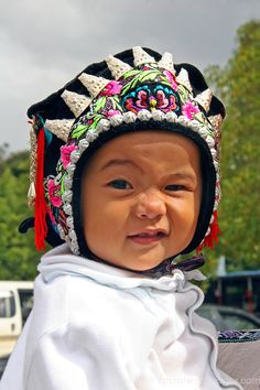 Asia, China, Kunming. Ethnic minority baby in traditional hat.