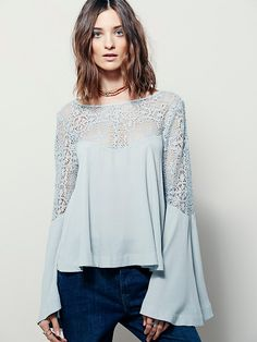 Movin On Up Top | Beautiful, swingy top featuring sheer crochet detail along the neckline and sleeves. Cutout at the back with button closure. Wide bell cuffs.