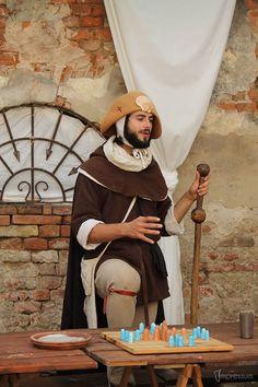 Een pelgrim, te herkennen aan zijn hoed en staf. Voor hem op tafel staat het bordspel Hnefatafl.