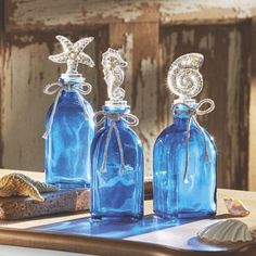 Set of 3 Blue Coastal Bottles - Trio of square bottom glass bottles with nautical glass stoppers with plastic gaskets from Country Door.