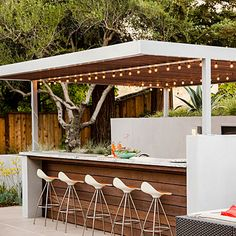 A total dream outdoor kitchen and bar. I love the clean lines, the sun blocking awning and the lights. With something like this we'd feel like we were on vacation. Forever. Which is awesome.