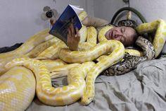 Эммануэль Танг читает книгу своей змее в своей спальне, Манила, Филиппины.