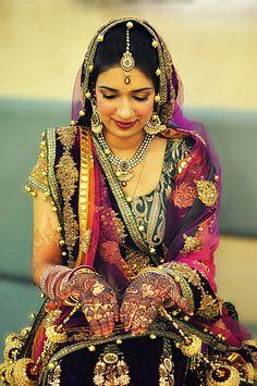 Beautiful intricate wedding mehndi design henna application on Indian or Pakitsani bride's hands for a Indian or Pakistani hindu wedding