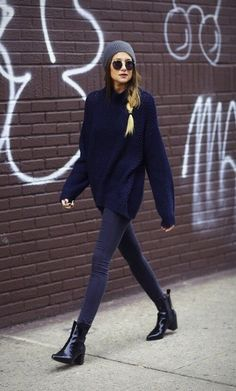 Blonde woman in skinny jeans and a navy blue oversized sweater