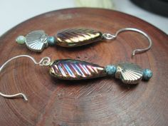 AN ELEGANT PAIR OF COPPER COLORED AND SILVER EARRINGS THAT CAN BE WORN FOR EVERYDAY.  THE TEARDROP SHAPE, COPPER COLORED, GLASS BEADS ARE TEXTURED WITH A FEATHER LIKE DESIG...