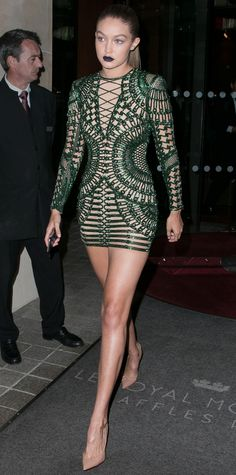 Gigi Hadid wowed at Balmain designer Olivier Rousteing's dinner in a sexy illusion nude Balmain mini embroidered with emerald green beadwork, styling it with slicked back strands, a vampy lip, and nude pumps.