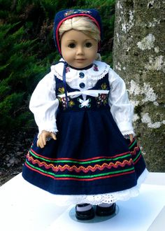 Our American girl is dressed for the Scandinavian Festival. She is wearing an outfit in the style of traditional Scandinavian dress. The main dress is made with a luxurious navy blue wool. It is decorated with flower appliques, rick rack, and satin ribbon. It has eyelets and ribbon to close the lined bodice in the front and it closes in back with navy blue buttons and hand-made button loops. I have also included two extra ribbons in case our American girl wants to change the color of the...