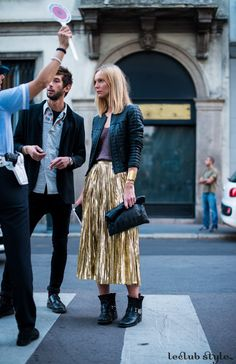 Womenswear Street Style by Ángel Robles. Fashion Photography from Milan Fashion Week. Woman wearing a pleated metallic midi skirt, leather jacket and boots. On the street, Via Monte Napoleone, Milano.