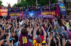 FC Barcelona players celebrate on an open top bus during their victory parade after winning the UEFA Champions League Final on June 7, 2015 in Barcelona, Catalonia.