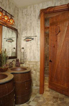 Boys Retreat- barrels house the hammered copper sinks and rustic top. The door was faux finished to resemble a ledge and braced outhouse door with half moon carved into it. Forest friends adorn the tile in the shower area.