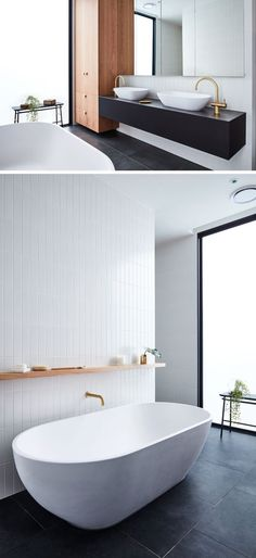 In this modern bathroom, black flooring and a black vanity contrast the white freestanding bathtub and accent tile wall, while the wood cabinets and a plant add a natural element. White Bathroom Cabinets, White Vanity Bathroom, Wood Bathroom, Wood Cabinets, Bathroom Flooring, Bathroom Interior, Bathroom Black, Bathroom Plants, White Cabinets