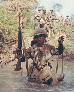 American soldiers crossing a river in Vietnam.