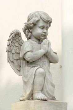 Cute winged Angel statue in praying pose with side view Stock Photo