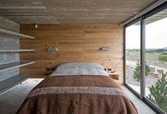sol en béton ciré, lambris mural en bois massif, lit double et baies vitrées