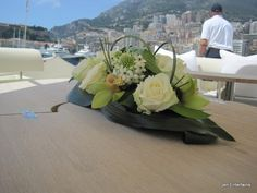 Low french flower arrangement with loops and a base of glossy leaves. Beautiful!