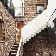 ~Mirrored walls and projecting staircases create optical illusions inside the brick-lined atrium of this apartment complex in Ghent, Belgium, by local office Atelier Vens Vanbelle...