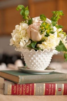 milk glass with old books, roses, stock, bells of ireland