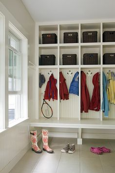 Custom built-in mudroom storage with integrated bench, beadboard back and gingerbread man coat hooks in Lexington, MA.