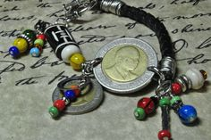 Leather and wire wrapped coin bracelet.  The bracelet contains one each 20 & 5 Schilling from Kenya and multi color glass bead dangles.  The connecting link contains one each carved wooden, howlite and glass bead.  Toggle clasp is attached.