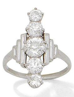 An Art Deco diamond dress ring, circa 1925. The graduating vertical row of old brilliant-cut diamonds, between baguette-cut diamond shoulders, mounted in platinum. #ArtDeco #ring