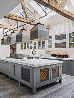 Industrial farmhouse kitchen with grey cabinets, galvanized industrial pendants over island, and wood beams. Kitchen