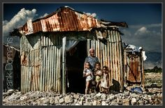 A single mother with her children and their hut in the slum of Ti Ayiti in Port-au-Prince, Haiti