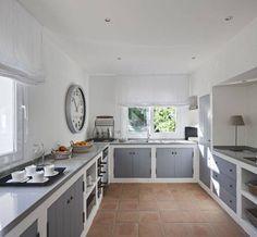 Piccola cucina in muratura, stile classico, realizzata con moduli fissi, top in marmo e sportelli colore grigio