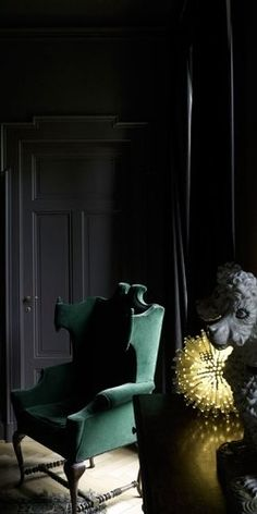 .Black paneled walls, green velvet wingback chair, brassy accents. Perfect.