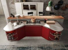 îlot de cuisine en rouge et acier inox, meuble d'angle discret et suspension industrielle