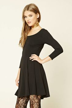 A stretch-knit dress featuring a skater silhouette, 3/4 sleeves, and a round neckline.