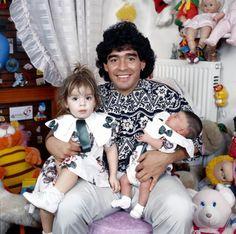 1989 Diego Maradona sitting in a small doll and cuddly toy infested bedroom with his daughters Dalma and Giannina in his arms. Diego Armando, International Soccer, Time And Tide, Nike Football, Couple Shoot, Cristiano Ronaldo, 1980s, Kids Toys, Sport