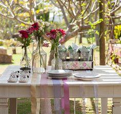 Com uma mesa de madeira linda como essa, a toalha se torna dispensável e é substituída por fitas de diferentes cores e materiais. Uma graça!