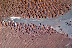 Frozen crests of sand break over the arid rock, Namibian coast, Africa.