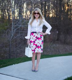 A pink floral skirt is paired with a white polka dot blouse for a fun pattern mixed business casual work look for spring.