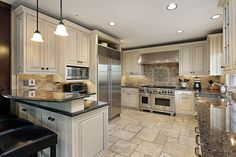 White engraved kitchen cabinets on light neutral tone tile floor with dark counter tops. Bar stools line the peninsula