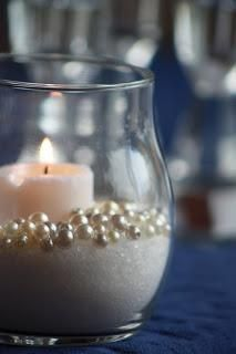 """An easy DIY wedding centerpiece idea: Sand (or sugar), faux pearls, & a 3"""" candle. Very elegant to use colored sand to match your wedding theme! #weddings #weddingdecorating #weddingsand #weddingcenterpiece #DIYwedding"""