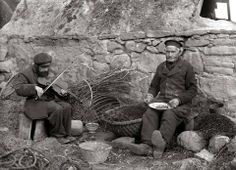 Blind Benjie, Finlayson playing his fiddle while his father baits a line outside their house in Cromarty. c1910