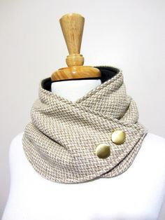 Made with a soft herringbone tan and white wool. Adorned with soft gold decorative buttons. Backed with gray fleece for added warmth. Secures around neck with snap. This neck warmer is a Christina Robinson original design. Please check out my policies section before making your purchase. http://www.etsy.com/shop/FashionCogs/policy?ref=shopinfo_policies_leftnav Thanks