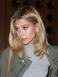 Hailey Baldwin opted to flaunt her taut and sexy abs in a flirty and polished casual ensemble that included a grey blouse with cropped hemline, pair of black jeans with ripped detailing at the knees and a long khaki trench coat that trailed almost down to her ankles as she stepped out for a night out on August 24, 2016.