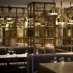 One of the major changes is the introduction of a gold framed distressed antique mirror installation, located opposite the bar at the rear of the main dining area which is now home to a new plush grey velvet banquette; the patina of the glass is set off nicely against the high shine of the brass pendant lights...