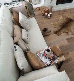 Si tu objetivo es crear una atmósfera acogedora para el salón, viste el sofá con plaids y cojines y añadirás comodidad con estilo.  Personalmente: pieles de animales no, gracias. Peron los tonos neutros combinados con la madera en esta imagen me aportan paz.