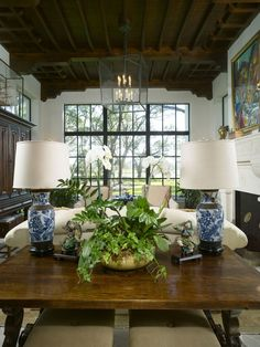 Mediterranean-Living-Room blue and white vase maps candle chandelier huge floor length windows