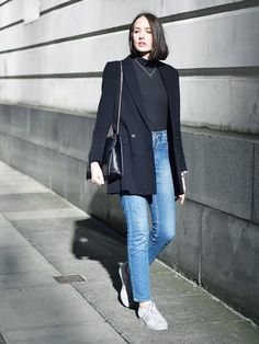 A black blazer is worn over a black turtleneck with blue jeans, a black shoulder bag, and white sneakers