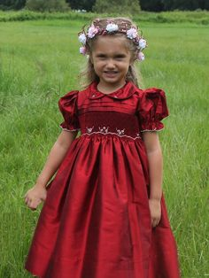 So absolutely stunning is this Ruby Red flower girl dress! Hand smocked on the bodice are petite white roses and their leaves. There is plaiting on the top of the bodice. A Peter Pan collar has matching smocked roses. The puffy sleeves are edged with delicate stitching. It also has covered buttons on the back as well as a tying sash. The skirt is lined. Perfect for a pageant, a wedding or any special occasion!