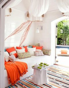 White, orange, green, turquoise and the outdoors...here is an interior designer created indoor room with all the breeziness of the outdoors. This living space easily provides a transition to an outside yard with a bright blue pool.