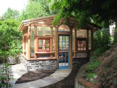 beautiful wood garden shed with walls of windows including arched window lights and a stone foundation