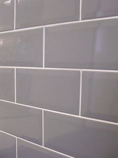 grey subway tile with white grout for behind stainless hood.